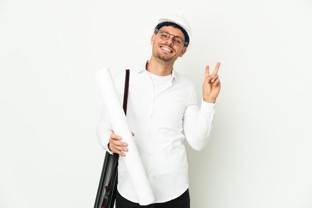헬멧과 지주 청사진 미소와 승리 기호를 보여주는 흰색 배경에 고립 된 젊은 건축가 남자