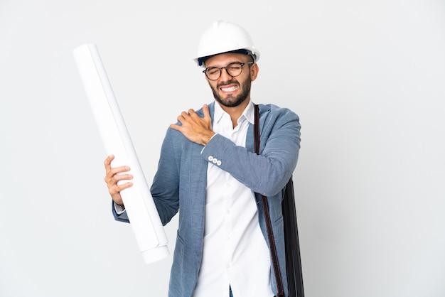 Молодой архитектор в шлеме и держит чертежи, изолированные на белом фоне, страдает от боли в плече за то, что приложил усилия