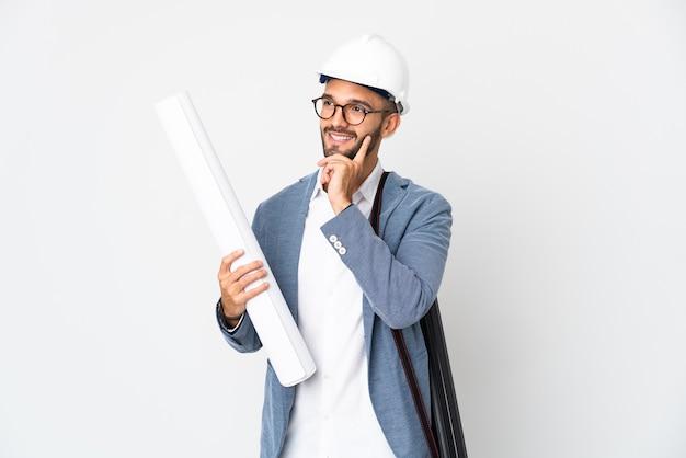 헬멧을 가진 젊은 건축가 남자를 찾는 동안 아이디어를 생각하는 흰색 배경에 고립 된 청사진을 들고