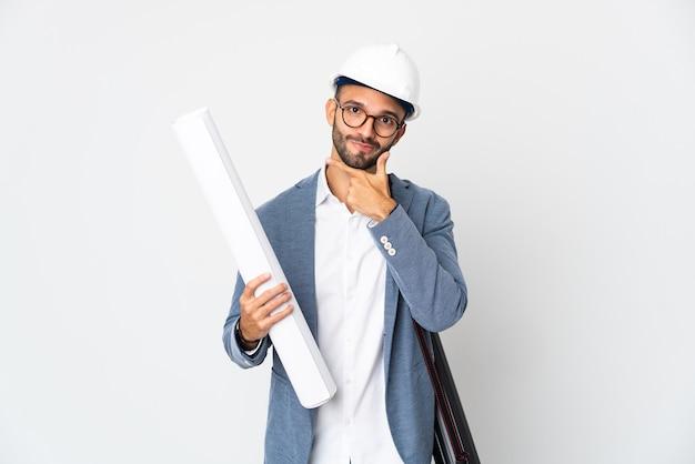 헬멧과 흰색 배경 생각에 고립 된 청사진을 들고 젊은 건축가 남자