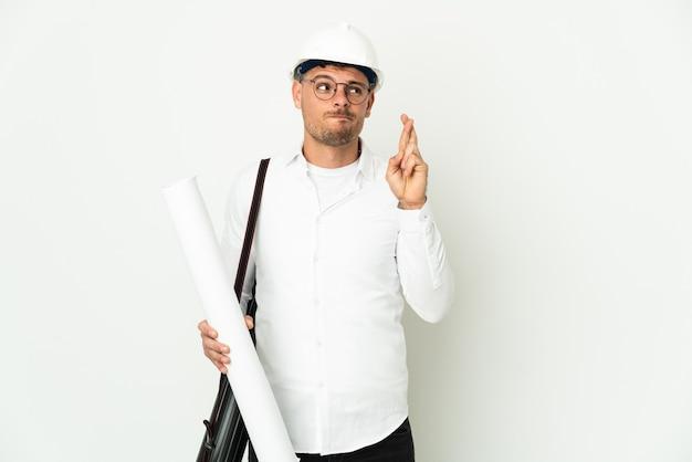 Молодой архитектор мужчина в шлеме и держит чертежи на белом фоне со скрещенными пальцами и желает лучшего