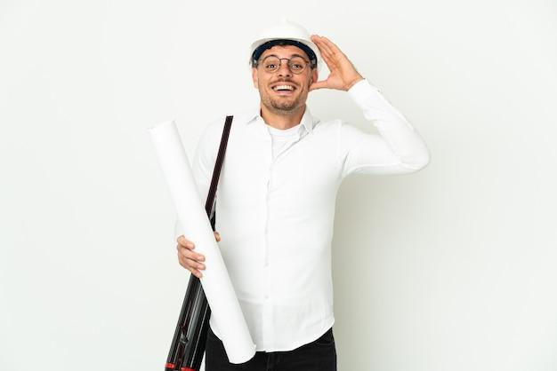 Молодой архитектор мужчина в шлеме и держит чертежи, изолированные на белом фоне с удивленным выражением лица