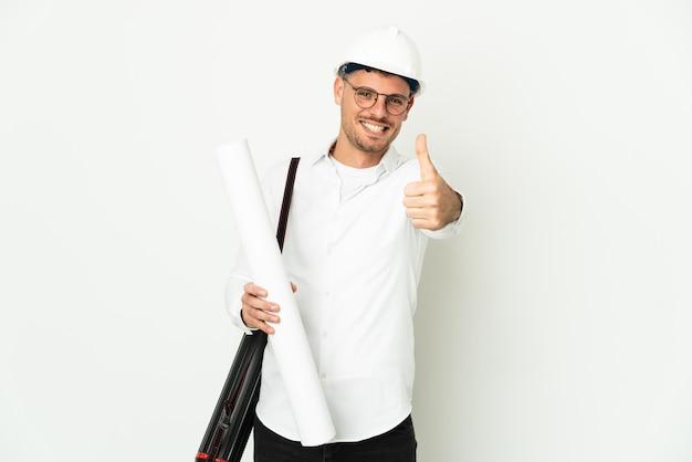 헬멧을 가진 젊은 건축가 남자와 좋은 일이 일어났기 때문에 엄지 손가락으로 흰색 배경에 고립 된 청사진을 들고