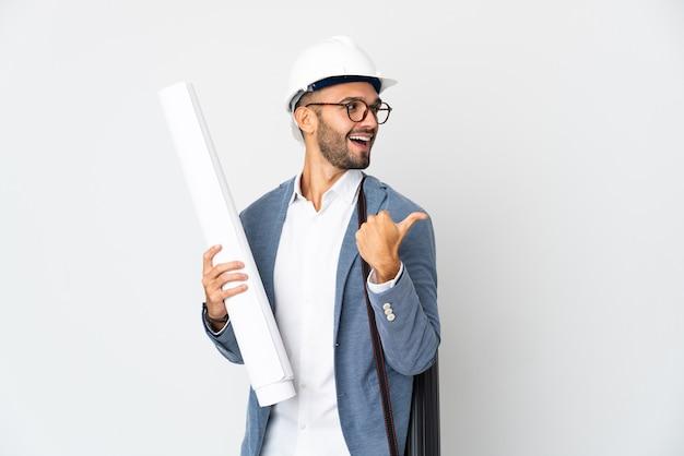 Молодой архитектор человек в шлеме и держит чертежи, изолированные на белом фоне