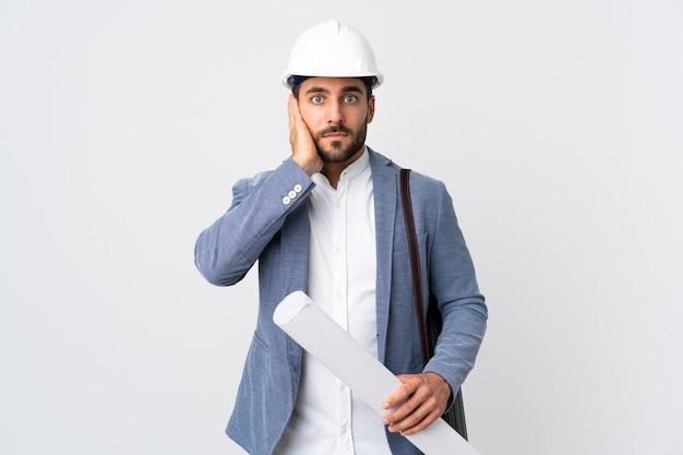 헬멧과 청사진을 들고 젊은 건축가 남자 좌절과 귀를 덮고 흰색에 고립