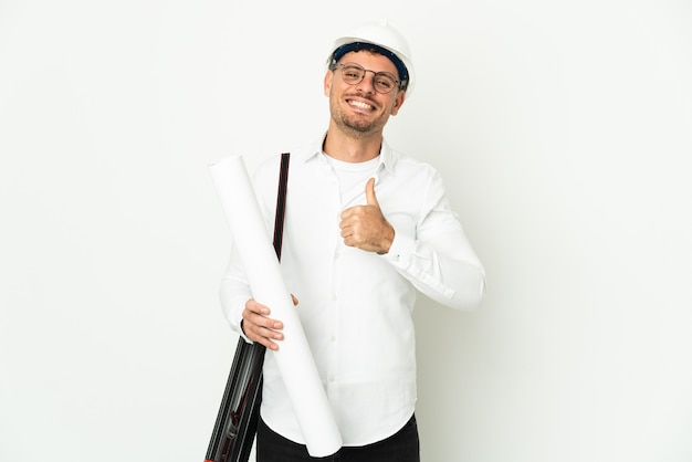 ヘルメットと親指を立てるジェスチャーを与える白で隔離の青写真を保持している若い建築家の男