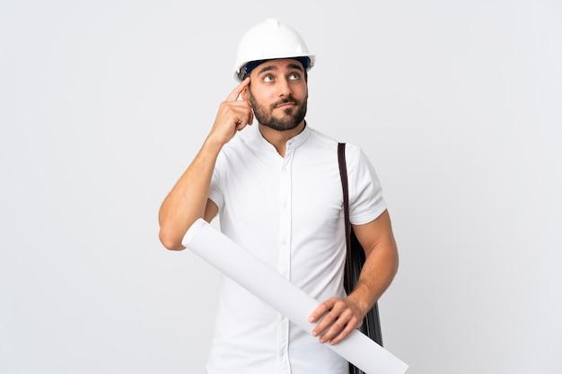 Молодой архитектор человек в шлеме и держит чертежи, изолированные на белом, сомневаясь и думая