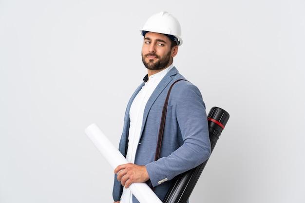 헬멧 및 흰색 절연 청사진을 들고 젊은 건축가 남자. 초상화