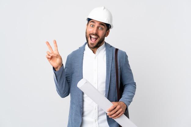 헬멧과 흰색 미소와 승리 기호를 보여주는에 고립 된 청사진을 들고 젊은 건축가 남자