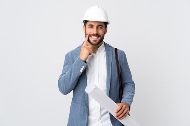 헬멧과 청사진을 들고 젊은 건축가 남자는 행복하고 즐거운 표정으로 웃고 흰색에 고립