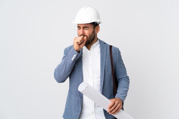 헬멧을 가진 젊은 건축가 남자와 많은 기침 흰 벽에 고립 된 청사진을 들고
