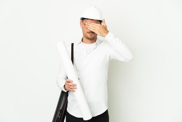 헬멧과 손으로 눈을 덮고 흰 벽에 고립 된 청사진을 들고 젊은 건축가 남자. 뭔가보고 싶지 않아