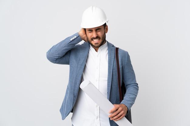 Молодой архитектор человек с шлемом и проведение чертежи, изолированные на белой стене разочарование и охватывающих уши
