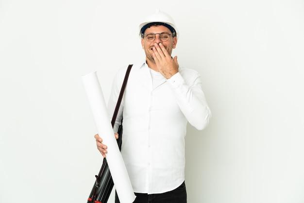 헬멧을 가진 젊은 건축가 남자와 흰 벽에 고립 된 청사진을 들고 행복하고 손으로 입을 덮고 웃고