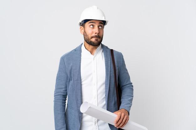 Молодой архитектор мужчина в шлеме и держит чертежи, изолированные на белой стене, сомневаясь, глядя вверх