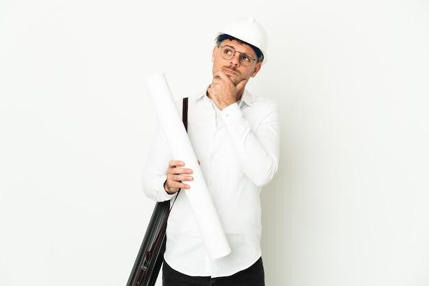 Молодой архитектор человек в шлеме и держит чертежи, изолированные на белой стене, сомневаясь