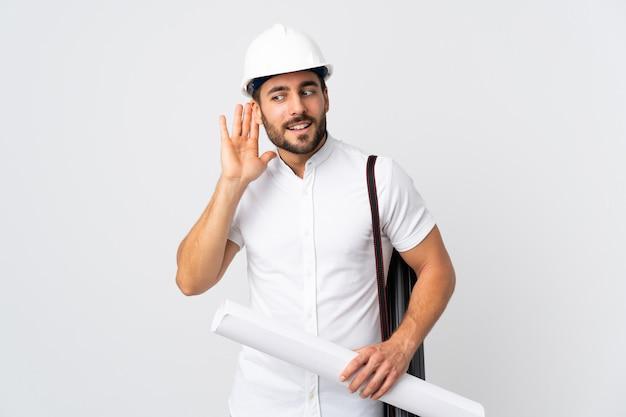 헬멧과 지주 청사진 젊은 건축가 남자 귀에 손을 넣어 뭔가를 듣고 흰 벽에 고립 된 청사진