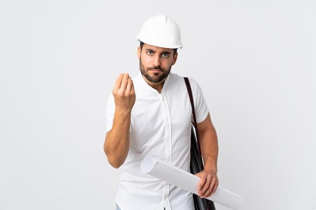 Молодой архитектор человек с шлемом и проведение чертежей, изолированных на белой стене, делая итальянский жест