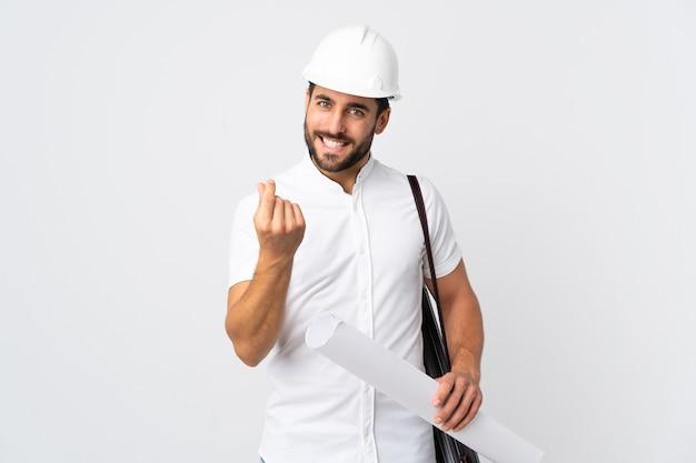 Молодой архитектор мужчина в шлеме и держит чертежи, изолированные на белой стене, делая денежный жест