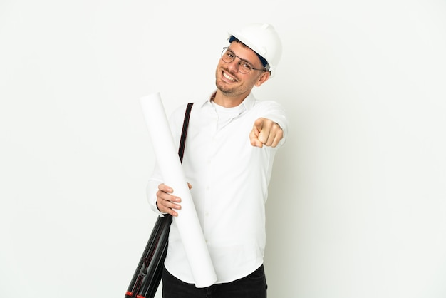 Молодой архитектор мужчина в шлеме и держит чертежи, изолированные на белой стене, указывая спереди с счастливым выражением лица