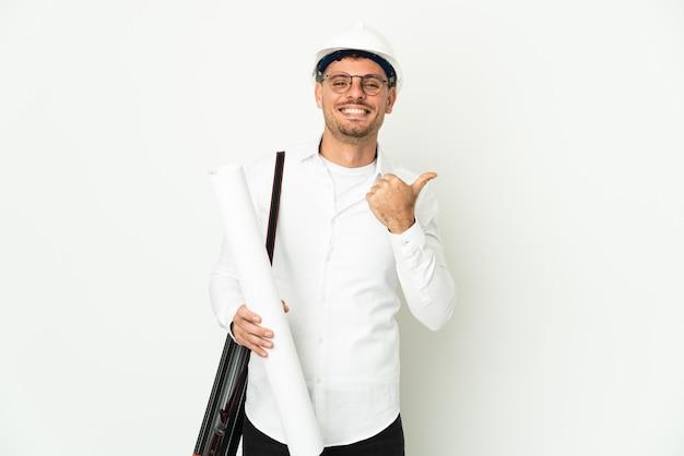 헬멧을 가진 젊은 건축가 남자와 제품을 제시하기 위해 측면을 가리키는 흰 벽에 고립 된 청사진을 들고