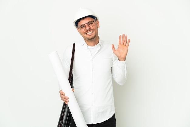 幸せな表情で手で敬礼する白い壁に分離されたヘルメットと青写真を保持している若い建築家の男