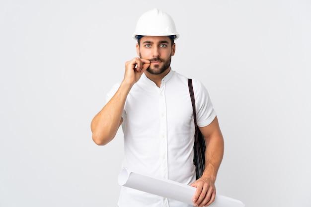 헬멧을 가진 젊은 건축가 남자와 침묵 제스처의 기호를 보여주는 흰 벽에 고립 된 청사진을 들고