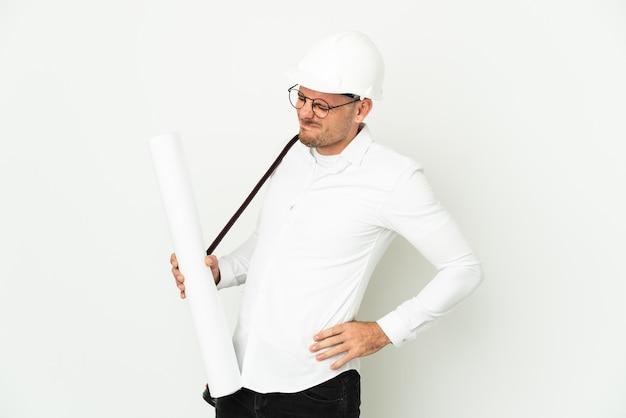 Молодой архитектор в шлеме и держит чертежи, изолированные на белой стене, страдает от боли в спине из-за того, что приложил усилия