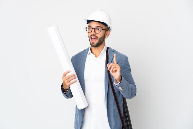 Молодой архитектор человек в шлеме и держит чертежи, изолированные на белой стене, думая, что идея указывает пальцем вверх