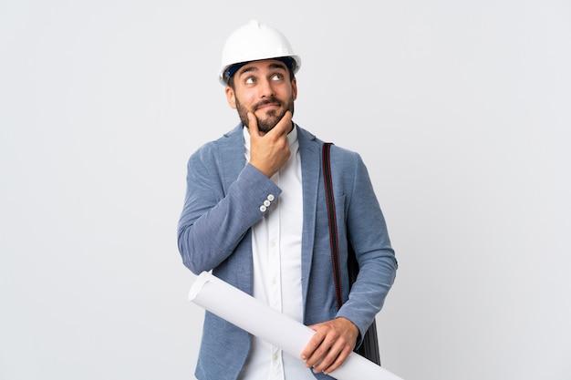 Молодой человек архитектора с шлемом и держать чертежи изолированные на белой стене думая идея пока смотрящ вверх