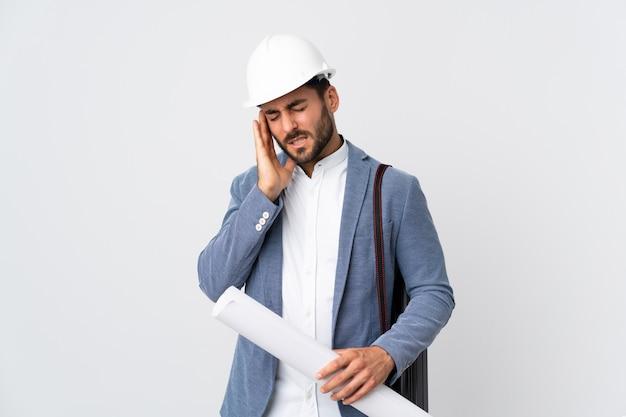 헬멧과 지주 청사진 두통으로 흰 벽에 고립 된 젊은 건축가 남자