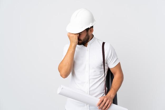헬멧과 지주 청사진 두통으로 흰색에 고립 된 젊은 건축가 남자
