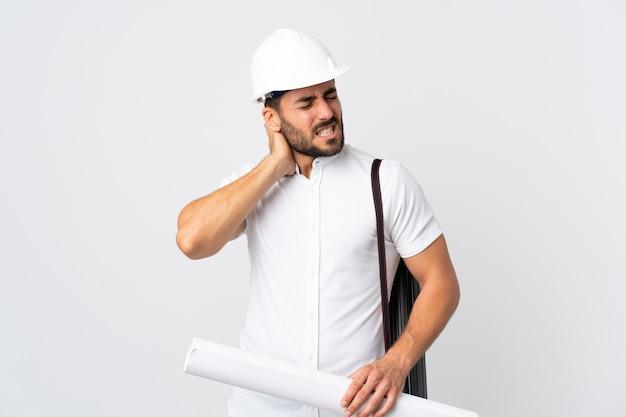 헬멧을 가진 젊은 건축가 남자와 neckache와 흰색에 고립 된 청사진을 들고