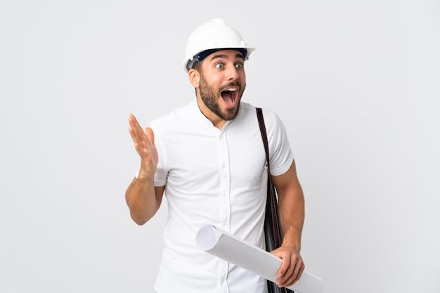 헬멧과 깜짝 표정으로 흰색에 고립 된 청사진을 들고 젊은 건축가 남자