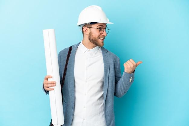 Молодой архитектор в шлеме и держит чертежи на изолированном фоне, указывая в сторону, чтобы представить продукт