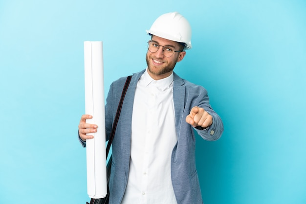 헬멧을 가진 젊은 건축가 남자와 행복 한 표정으로 고립 된 포인팅 전면에 청사진을 들고