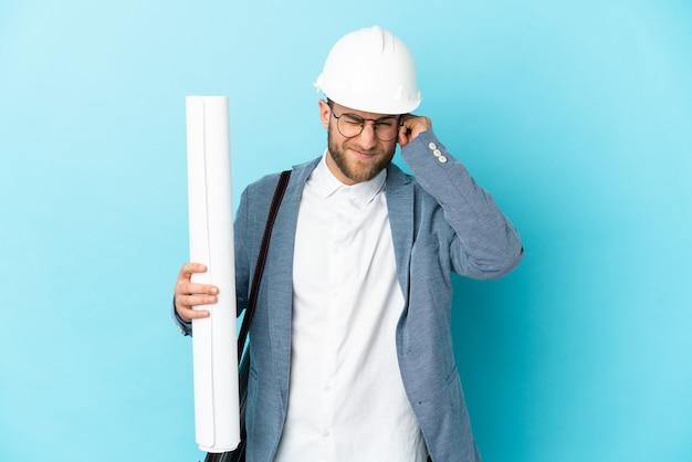 헬멧 젊은 건축가 남자 좌절과 귀를 덮고 고립 된 벽에 청사진을 들고