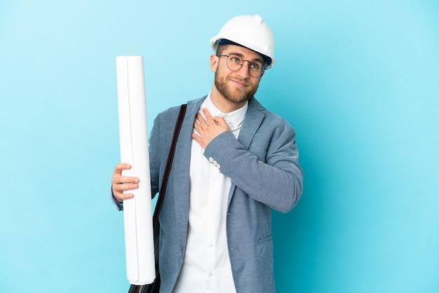 헬멧을 가진 젊은 건축가 남자와 웃고있는 동안 찾고 고립 된 벽 위에 청사진을 들고