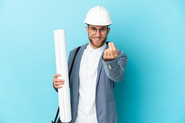 Молодой архитектор в шлеме и держит чертежи над изолированной стеной, делая денежный жест