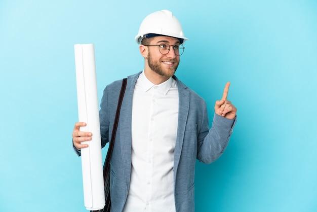 헬멧과 좋은 아이디어를 가리키는 격리 된 벽 위에 청사진을 들고 젊은 건축가 남자