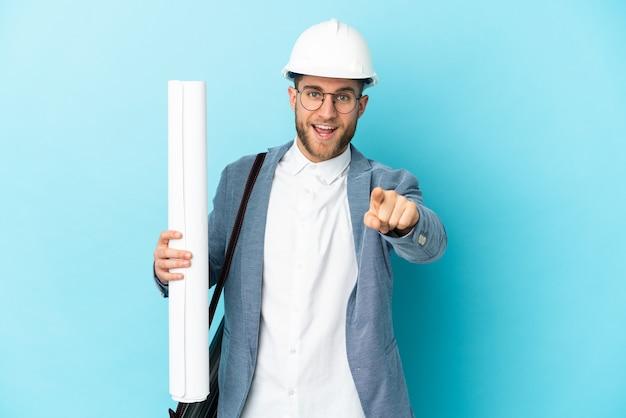 헬멧과 격리 된 벽에 청사진을 들고 젊은 건축가 남자 놀라게하고 앞을 가리키는