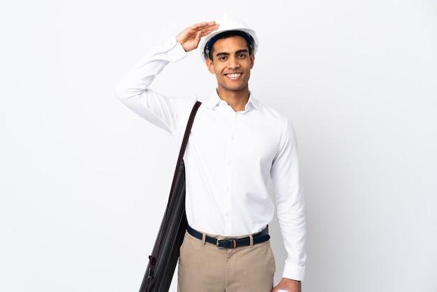 ヘルメットと孤立した白い壁に青写真を保持している若い建築家の男_幸せな表情で手で敬礼