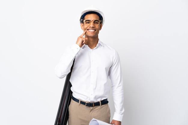 헬멧을 가진 젊은 건축가 남자와 격리 된 흰 벽에 청사진을 들고 행복하고 즐거운 표정으로 웃고