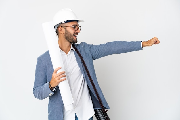 Young architect man with helmet and holding blueprints isolated on white background giving a thumbs up gesture