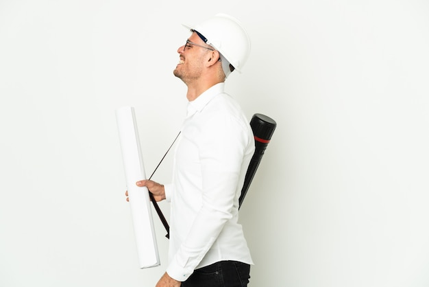 Young architect man with helmet and holding blueprints isolated on white background laughing in lateral position