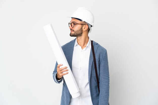 Young architect man with helmet and holding blueprints isolated on white background looking to the side