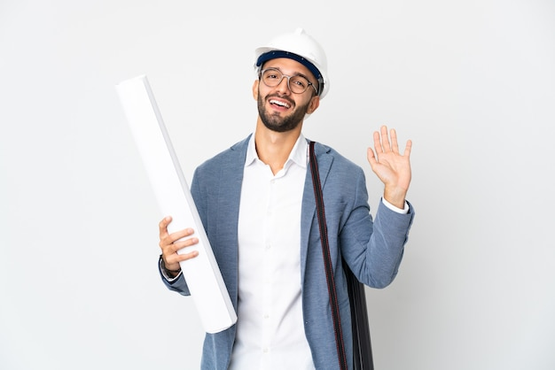 Young architect man with helmet and holding blueprints isolated on white background saluting with hand with happy expression