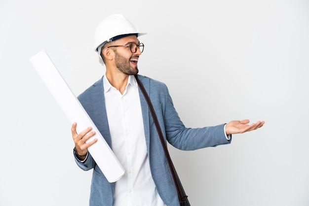 Young architect man with helmet and holding blueprints isolated on white background with surprise expression while looking side