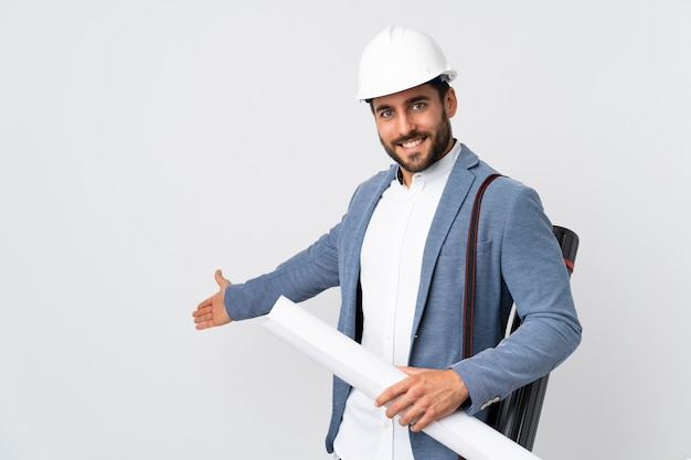 Young architect man with helmet and holding blueprints isolated on white wall extending hands to the side for inviting to come