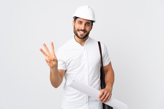 Young architect man with helmet and holding blueprints isolated on white wall happy and counting three with fingers